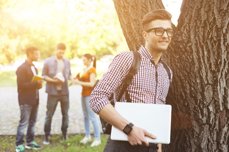 university life: Cheerful male student is enjoying university life. He is standing near a tree and holding a laptop. The man is dreaming and smiling. His friends are talking on background Stock Photo