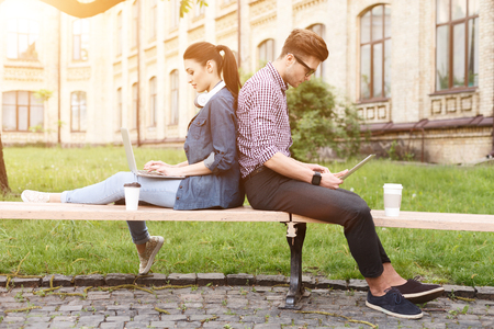 seriousness: Cheerful young man and woman are sitting on bench while leaning their back together. They are using laptops with concentration. Woman is smiling. Man is reading with seriousness
