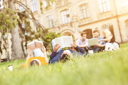 university life: Enjoying university life. Cute young students are lying on grass. Man and woman are reading book with relaxation. Their friends are sitting and using laptop on background Stock Photo