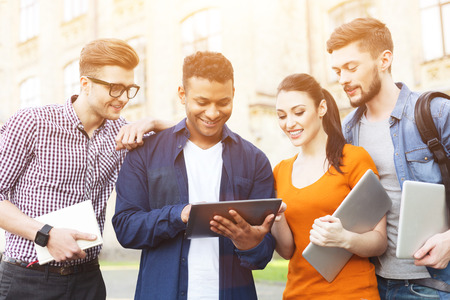 university life: Cheerful four students are enjoying university life. Young man is holding a tablet. His friends are looking at it with interest and smiling. They are carrying laptops and book