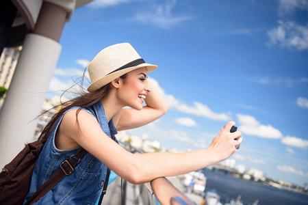 De onbezorgde jonge vrouw fotografeert rive landschap in stad. Ze staat en raakt haar hoed aan. Meisje lacht vrolijk Stockfoto