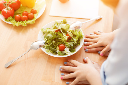 them: Top view of arms of mother and daughter lying on table near plate with salad, cooking by them