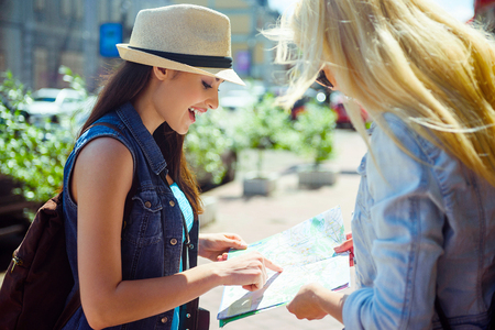 passerby: Cute female tourist is asking the way in passer-by. She is pointing finger at map and smiling. Girl is standing in city Stock Photo