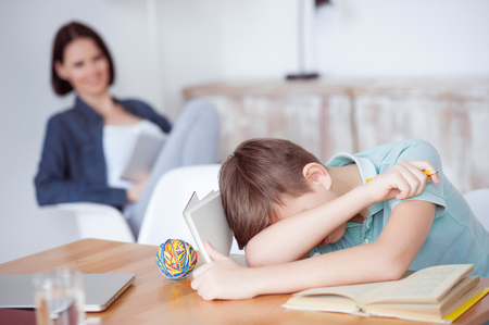 sleeping tablets: Too many study sessions. Young boy feeling asleep after hard studying with her mother in background, using digital tablet