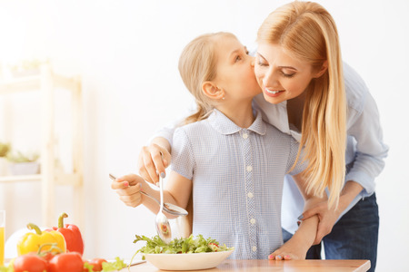 Mornings with mother are the best. Daughter kissing mother on cheek while making vegetable salad in kitchen Reklamní fotografie - 58808524