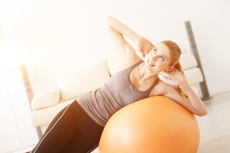 ball stretching: Having a good stretch. Sporty young woman lying on swiss ball doing stretching exercises at home Stock Photo