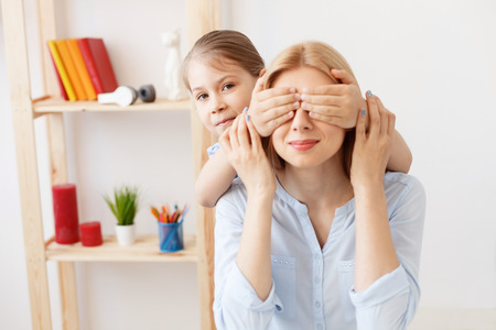 her: Family playtime. Little girl playfully putting her hands over eyes of her mother, playing at home