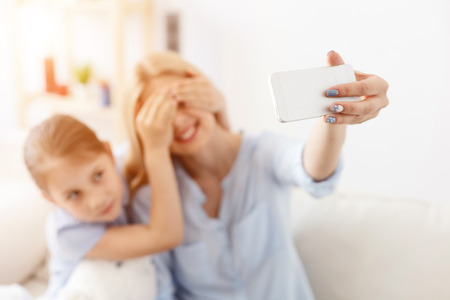 cherishing: Cherishing every moment together. Smiling mother and daughter taking selfie while spending time at home