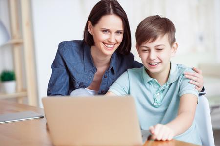 Aiutare con i compiti. Primo piano di felice madre sorridente e suo figlio adulto con laptop