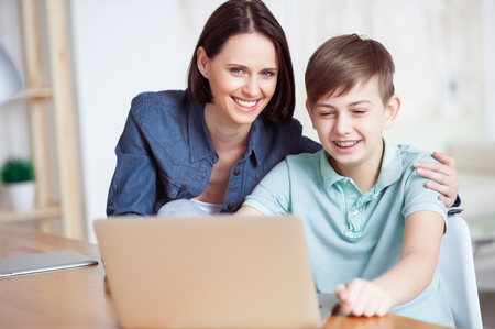Helping with homework. Close up of happy smiling mother and her adult son using laptop