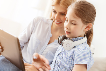 everyone: Technology has something for everyone. Young mother showing her daughter how to use digital tablet Stock Photo