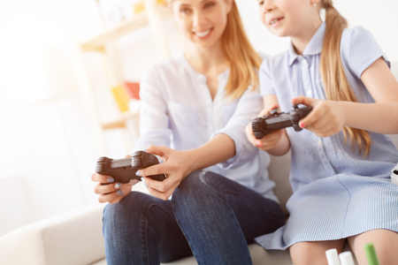 game time: Game time. Portrait of happy smiling woman playing video game with her daughter at home Stock Photo