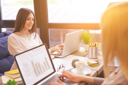 Le giovani donne felici stanno scrivendo sui computer portatili con concentrazione. Sono seduti al tavolo del caffè e sorridono