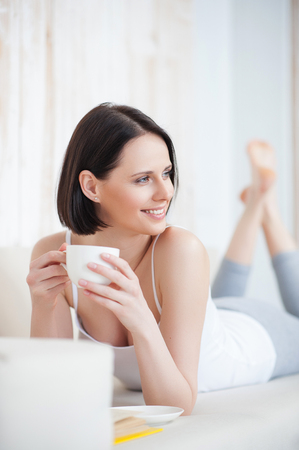 leisurely: My idea of leisurely day. Attractive young woman drinking tea while reading book, lying on sofa Stock Photo