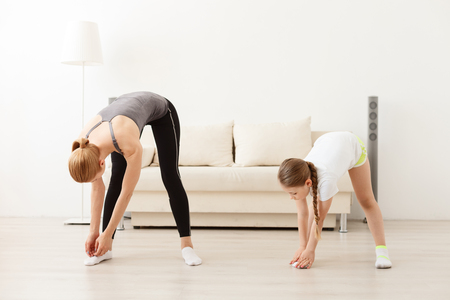 I can touch my toes. Young mother and daughter doing doing fitness exercises at home Stock Photo