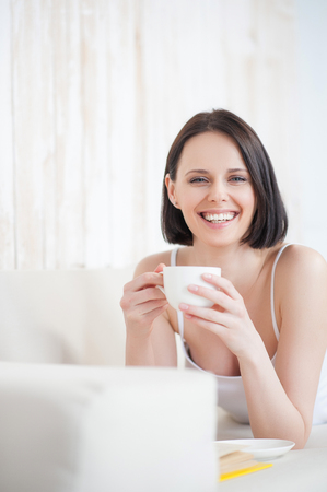 easygoing: Lounging with good book. Mature woman drinking tea and reading book on couch, smiling and looking at camera