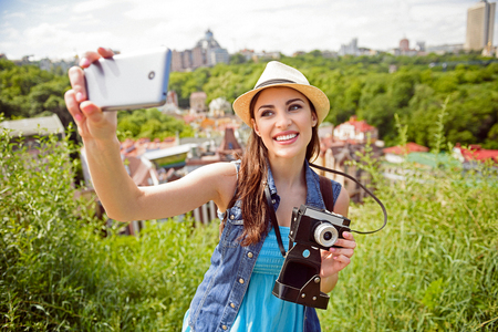 i am here: Here I am. Beautiful young woman is making selfie on a mobile phone. She is standing and holding a camera. Girl is laughing
