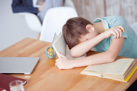 taking nap: I am so tired. Top view of little boy taking nap in middle of difficult homework, sitting at desk Stock Photo