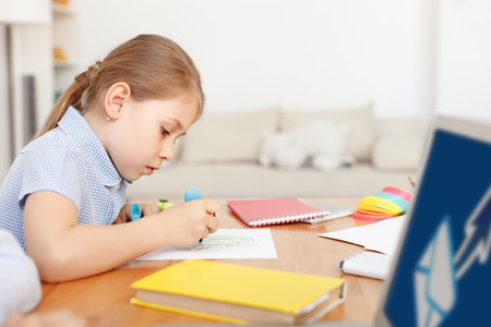 enthusiasm: When boredom strikes, creativity takes over. Little girl drawing in notebook with enthusiasm, using marker, sitting at desk