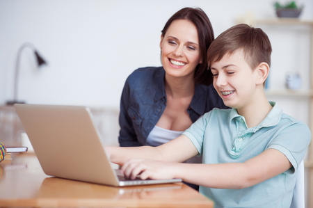 too fast: Growing up too fast. Happy boy using laptop with his mother, sitting at desk at home Stock Photo
