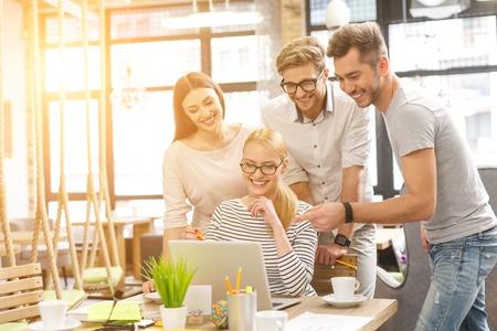 陽気な若い同僚は、新しいプロジェクトを計画しています。喜びでノート パソコンを見ていては立っています。女性は机に座っていると笑顔