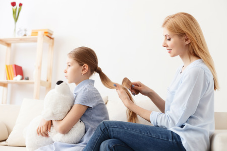 Hairstyle for my princess. Young mother sitting on sofa and combing hair of her daughter