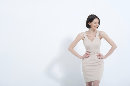 She owns that dress. Waist up studio shot of attractive woman in cream dress, isolated on white background Stock Photo