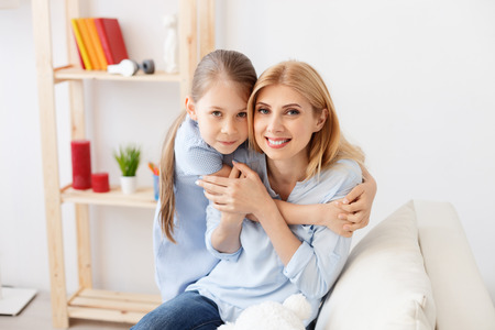 mother to be: Be good girl for me. Cute little girl smiling while hugging her mother tightly, sitting on sofa