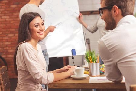 男性と女性が話していると笑顔は幸せ。テーブルに座って、幸せでお互いを見ています。同僚が立っているとボードに近いプロジェクトについて議論します。