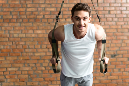 body built: Attractive fit man doing push-ups with trx straps in gym. He is looking at camera and smiling