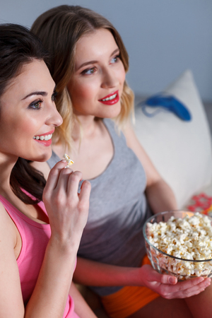Pretty girls are watching television with interest at home. They are eating popcorn and smiling