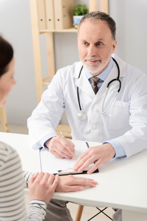 recommendations: Handsome middle aged doctor making recommendations for woman, looking at her smiling