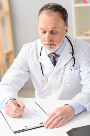 carefully: Working hard for his patients. Portrait of mature doctor carefully checking patients medical chart, sitting at desk Stock Photo