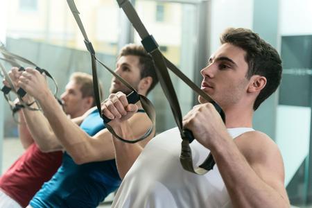 강한 젊은이들이 집단으로 운동하고 있습니다. 그들은 trx 스트랩으로 팔 굽혀 펴기를하고 있습니다. 남자들은 서서 자신있게 기대하고있다.