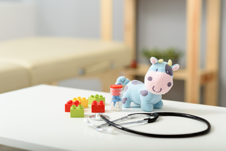 prescribe: Close up of plush toy and pills with stethoscope device on top of white table