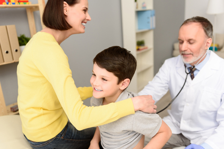 gently: Shot of mature pediatrician gently examining young boy with stethoscope at his office