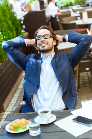arms behind head: Happy young businessman is relaxing in restaurant. He is dreaming and smiling. Worker is sitting while raising arms behind head