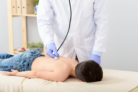 stethoscope boy: Mature pediatrician examining young boy, lying on using stethoscope Stock Photo