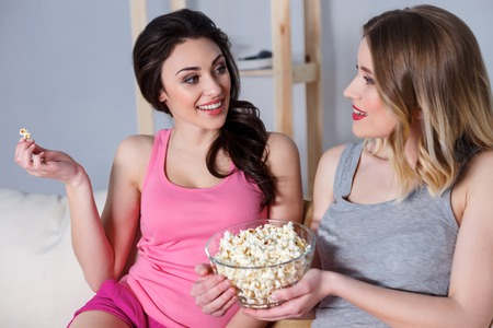 Best friends are talking and smiling. They are sitting on sofa and smiling. Girls are eating popcorn while watching movie Stock Photo