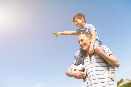 Cheerful grandfather and child are resting in the nature and smiling. The boy is sitting on male shoulders and pointing finger forward with interest. Mature man is standing and holding ball 免版税图像
