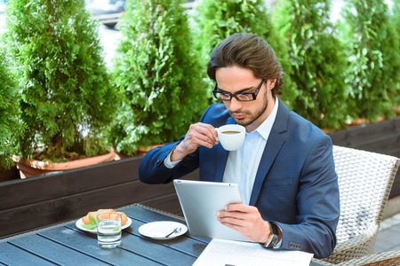 seriousness: Busy young businessman is using a tablet with seriousness. He is drinking coffee and sitting at table in restaurant Stock Photo