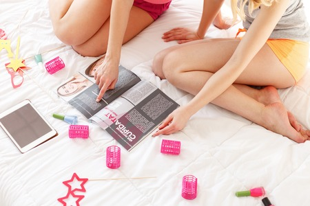 fashion magazine: Close up of carefree young women making pajama party. Girl is sitting on bed and pointing finger at fashion magazine