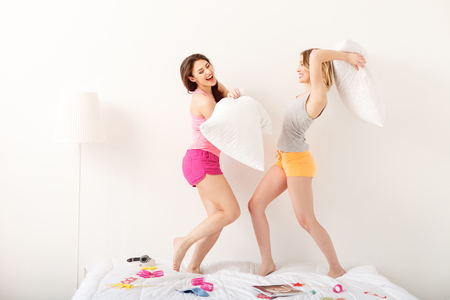 women fighting: Carefree young women fighting with pillows at pajama party. They are standing on bed and smiling Stock Photo