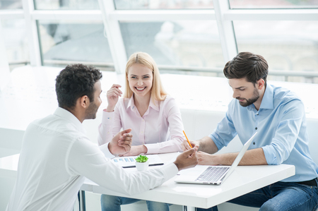 combining: Combining their creative ideas. Group of cheerful business people in smart casual wear working together while sitting at table