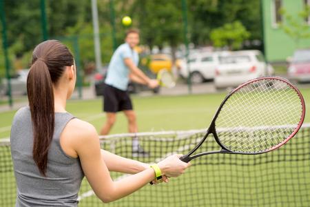 陽気な女と男は、コートでテニスを遊んでいます。ネットの反対側に立って、ラケットを保持しています。雌の背中に焦点を当てる
