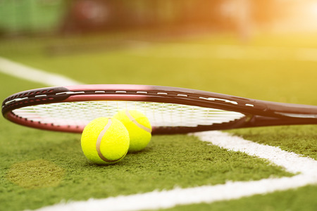 racquet: Close up of two tennis balls under racquet on lawn Stock Photo