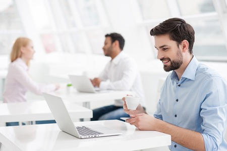 work environment: I love work environment. Smiling young male designer having coffee while sitting at his office desk with colleagues working in background Stock Photo