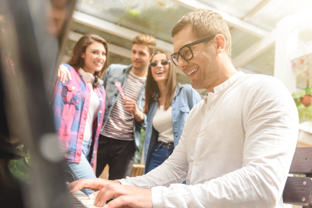 I was born to be pianist. Handsome guy in glasses playing piano for his friends, standing beside him Stock Photo