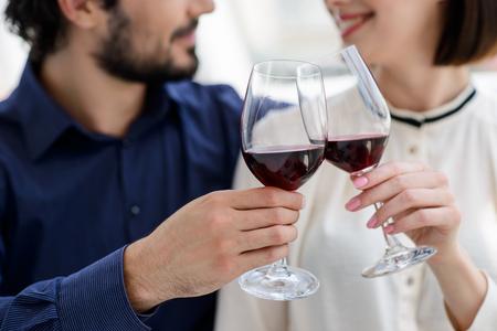 Aclamaciones. Alegres copas tintinean de los pares casados ??y sonriente. El hombre está sentado y abrazando mujer. Centrarse en vasos de vino