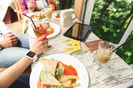 view to outside: Start day with friend. Top view of hand of woman holding glass with cocktail, wearing smart clock near digital tablet and lunch on wood table